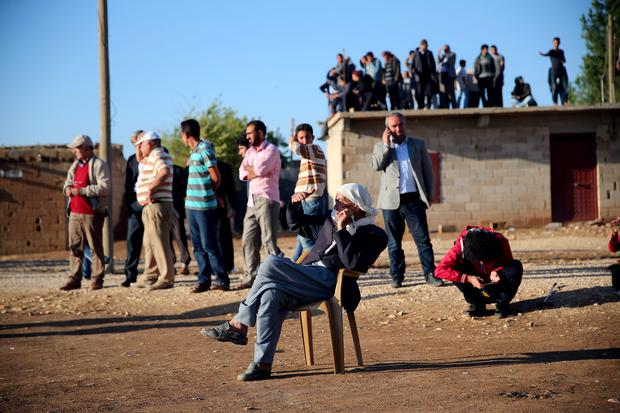 Border village of Alizar residents keep guard during the night and day wait in fear from mortar fired from Islamic State fighters as they tightened their siege of the strategic town of Kobani on Syria's border with Turkey on September 29, 2014 in Sanliurfa, Turkey. (Photo by Stringer/Getty Images)