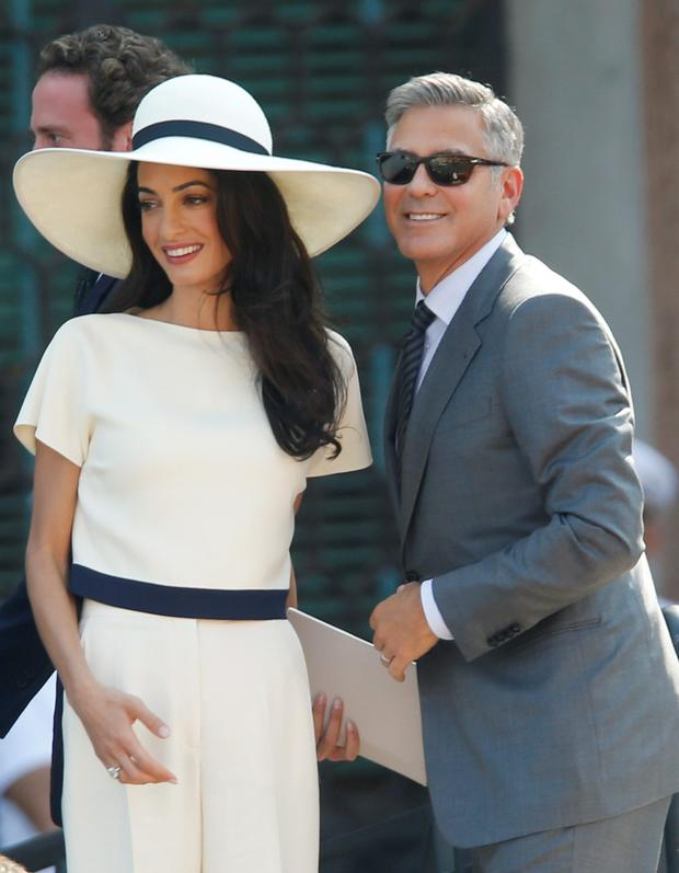 George Clooney, flanked by his wife Amal Alamuddin, arrives at the city hall for their civil marriage ceremony in Venice, Italy