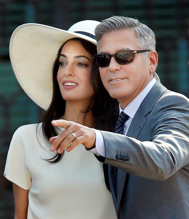 George Clooney, right, flanked by his wife Amal Alamuddin, arrives at the Cavalli Palace for the civil marriage ceremony in Venice