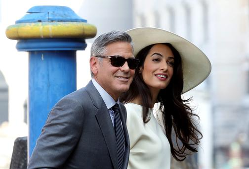 George Clooney, flanked by his wife Amal Alamuddin, arrives at the city hall for their civil marriage ceremony in Venice, Italy, Monday, Sept. 29, 2014.