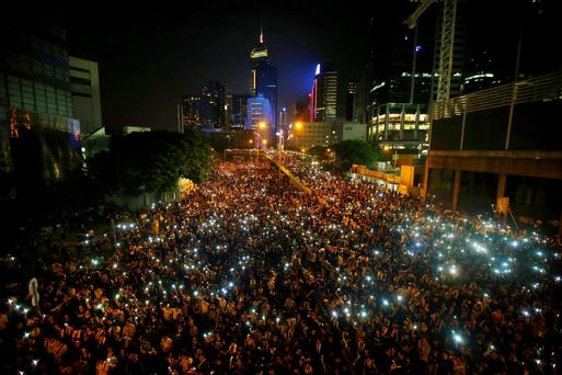 Protesters hold their mobile phones as they block the main street to the financial Central district, outside the government headquarters, in Hong Kong