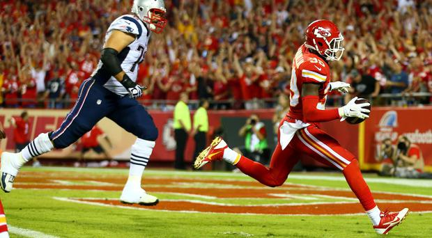 Husain Abdullah #39 of the Kansas City Chiefs scores a touchdown after an interception against the New England Patriots at Arrowhead Stadium but there was a flag on the play
