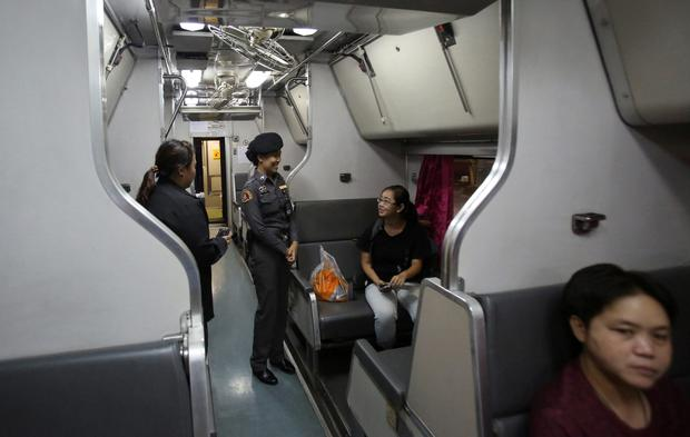 Female railway police officers talk with a passenger at a train carriage for women and children, at Hua Lamphong train station in Bangkok, Thailand, The State Railway of Thailand introduced a womens-only carriage on main routes for overnight trains following the rape and murder of a 13-year-old girl on an overnight train in July