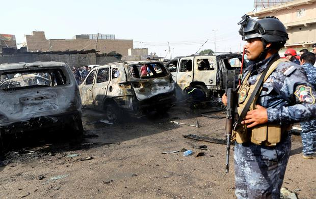 Security forces inspect the site of a car bomb explosion in the town of Ashar, in the Basra region, 550 kilometers (340 miles) southeast of Baghdad, Iraq