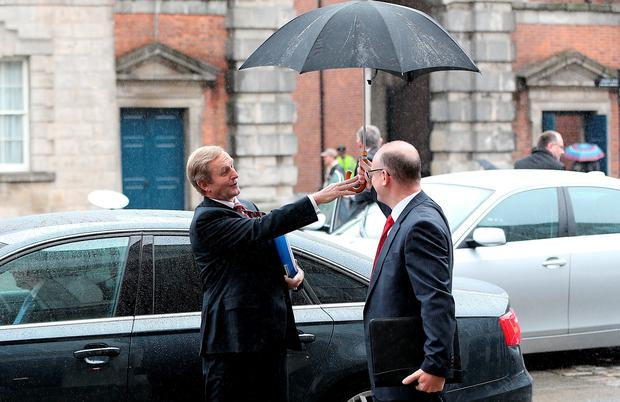 Taoiseach Enda Kenny declines the offer of an umbrella despite the inclement weather as he arrives at Dublin Castle for the North South Ministerial Council Meeting.