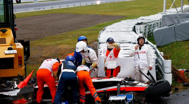 Medics attend to Jules Bianchi in his car after the F1 driver hit a recovery tractor