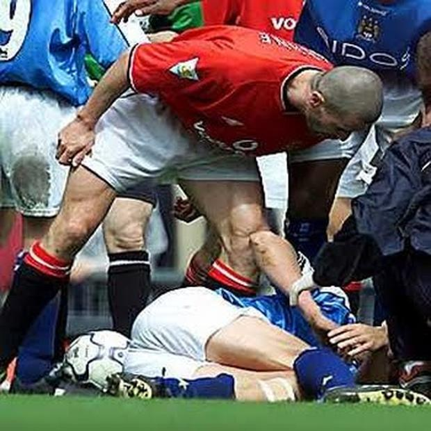 Roy Keane stands over Alf Inge Haaland during a Manchester derby clash in 2000