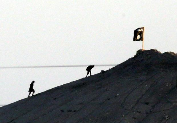 In this image shot with an extreme telephoto lens and through haze from the outskirts of Suruc at the Turkey-Syria border, militants with the Islamic State group are seen after placing their group's flag on a hilltop at the eastern side of the town of Kobani, Syria, where fighting had been intensified between Syrian Kurds and the militants of Islamic State group. AP Photo