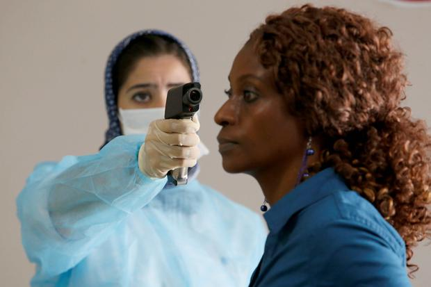 A Moroccan health worker uses a thermometer to screen a passenger at the arrivals hall of the Mohammed V airport in Casablanca. AP