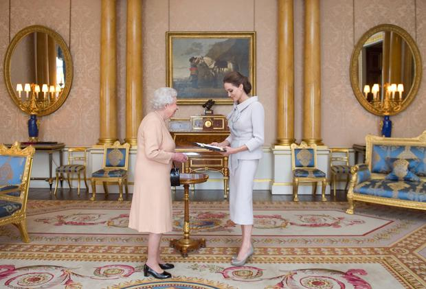 Actress Angelina Jolie is presented with the Insignia of an Honorary Dame Grand Cross of the Most Distinguished Order of St Michael and St George by Queen Elizabeth II in the 1844 Room at Buckingham Palace, London. Photo: Anthony Devlin/PA Wire
