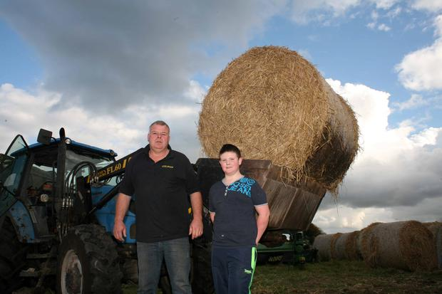 Michael Fitzmaurice pictured working the farm with his son Patrick as the Roscommon South Leitrim by-election count continues at Roscommon Gaels GAA club. Photo Brian Farrell
