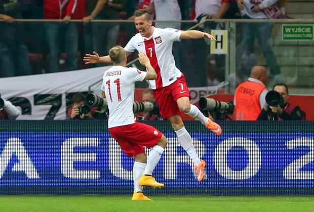 Arkadiusz Milik celebrates with Kamil Grosicki after scoring Poland's opening goal in their Euro 2016 qualifier against Germany in Warsaw. Photo: Alexander Hassenstein/Bongarts/Getty Images