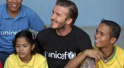 British soccer player of the Los Angeles Galaxy and UNICEF Goodwill Ambassador David Beckham poses with former Filipino street children during his visit to a UNICEF-supported government center for children rescued from the streets Friday Dec. 2, 2011 in a suburb of Manila in the Philippines.
