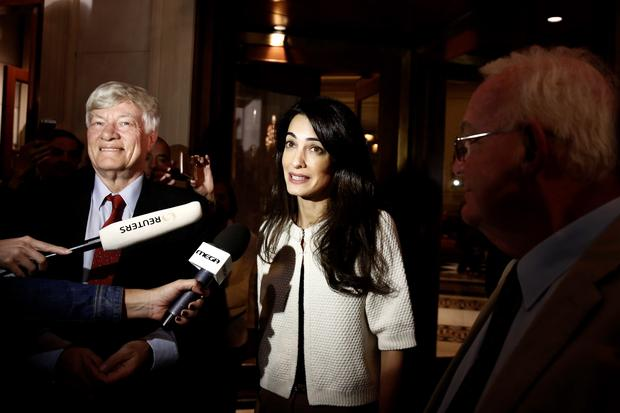 Human rights lawyer Amal Alamuddin Clooney (C) makes statements as Geoffrey Robertson (L), head of Doughty Street Chambers, and David Hill, head of the International Committee for the Reunification of the Parthenon Marbles, look on after their arrival at a hotel in Athens October 13, 2014. Lebanese-born Alamuddin, fresh from her marriage to Hollywood heart-throb George Clooney last month