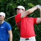 Rory McIlroy hits his tee shot on the third hole as Martin kaymer looks on during the first round of the PGA Grand Slam of Golf in Bermuda