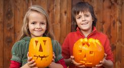 Kids with freshly carved Halloween pumpkins