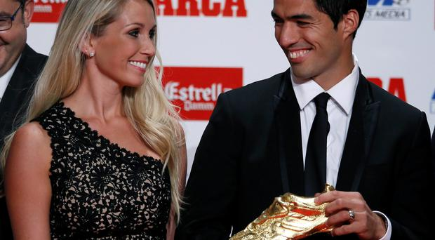 Barcelona's Luis Suarez poses with the Golden Boot trophy next to his wife Sofia Balbi. Suarez shares the trophy with Real Madrid's Cristiano Ronaldo with a goal tally of 31 goals in Europe's domestic leagues last season.