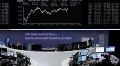 Traders are pictured at their desks in front of the DAX board at the Frankfurt stock exchange October 17, 2014