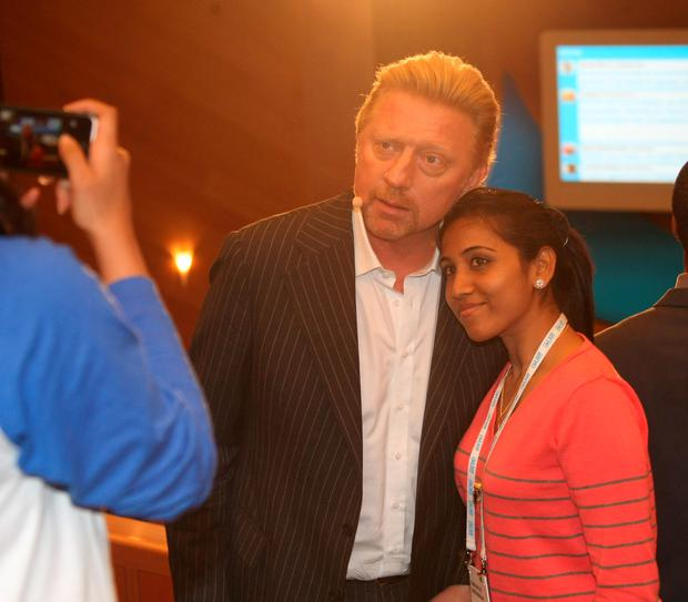 Boris Becker takes a photo with a delegate at the One Young World Summit