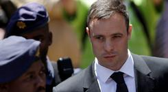 Oscar Pistorius escorted by police officers leaves the high court in Pretoria, South Africa, on Friday. Following the testimony hearing, Judge Thokozile Masipa is expected to announce Pistorius' sentence on Tuesday after she found him guilty last month of culpable homicide for negligently killing Steenkamp, but acquitted him of murder (AP Photo/Themba Hadebe)