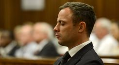 Oscar Pistorius stands as he listens to his judgement in the Pretoria High Court on October 21, 2014, in Pretoria, South Africa. Judge Thokozile Masipa handed down her sentence today. Pistorius was sentenced to five years in prison