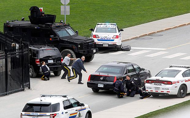 Police officers take cover near Parliament Hill (Chris Wattie/Reuters)