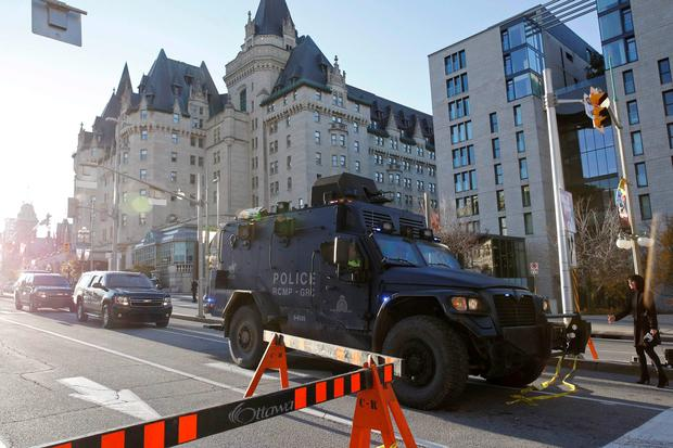 A Royal Canadian Mounted Police vehicle passes the Fairmont Chateau Laurier as it leaves a secure area downtown following shootings in Ottawa October 22, 2014