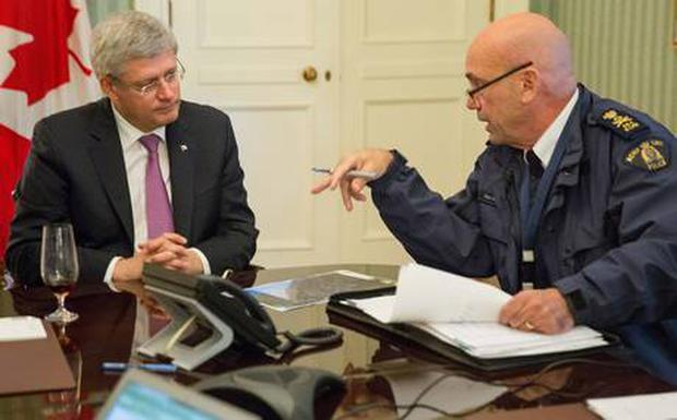 Head of RCMP Bob Paulson briefs Canadian prime Minister Stephen Harper on the shootings at Parliament Hill in Ottawa