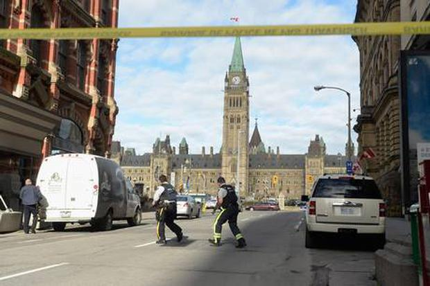 Police secure the scene of a shooting on Parliament Hill in Ottawa