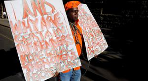 Prisoner rights activist Miles Bhudu holds placards outside the court where Oscar Pistorius was being tried in Pretoria October 21, 2014. As Pistorius spent his first day behind bars this week, a suspected child rapist and murderer went on trial at the same Pretoria court in a case that has also provoked fierce debate about crime and punishment in post-apartheid South Africa. Although the two defendants, one wealthy and white, the other poor and black, are from opposite ends of a still-divided society, both cases have revealed an alarming lack of faith in the justice system of the