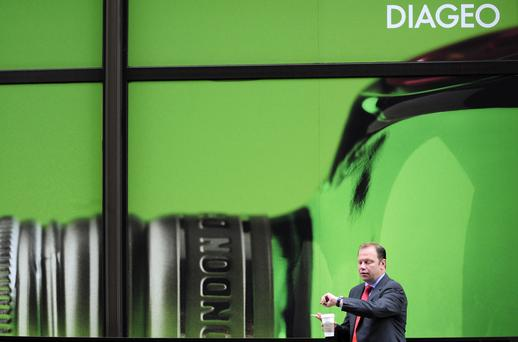 A worker walks past the headquarters of Diageo in London.