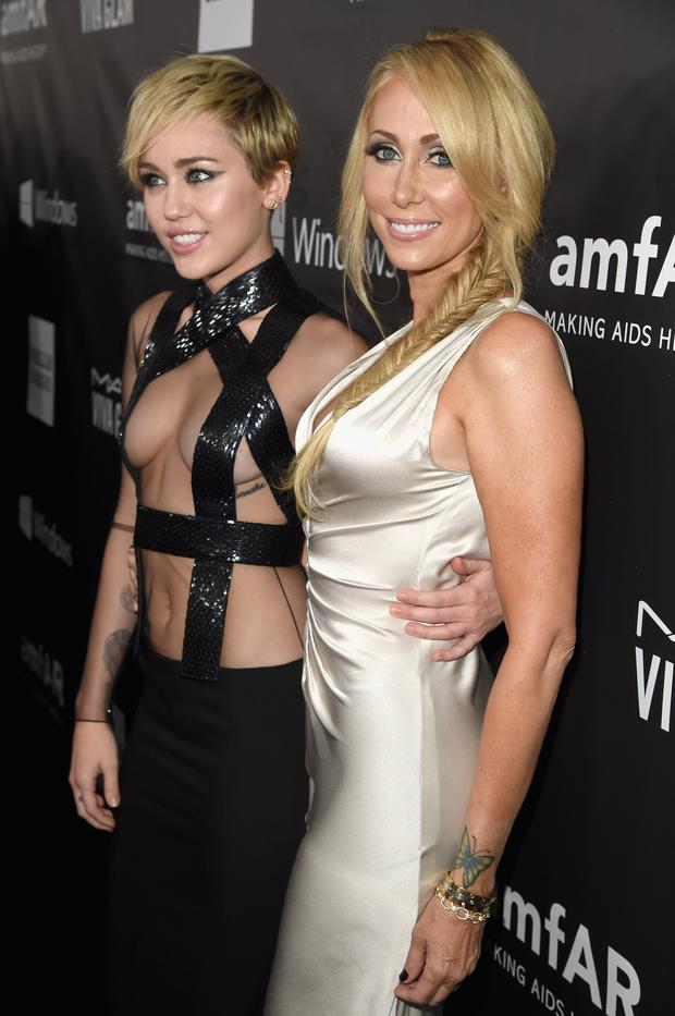 Singer Miley Cyrus (L) and Tish Cyrus attend the 2014 amfAR LA Inspiration Gala at Milk Studios