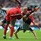Liverpool's Mario Balotelli and Newcastle United's Steven Taylor battle for the ball. Owen Humphreys/PA Wire