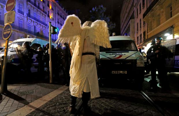 A demonstrator dressed as an angel faces French riot police officers during a rally in Marseille, October 31, 2014.