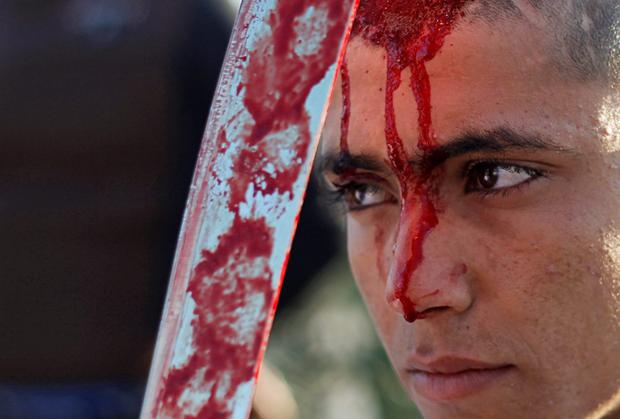 An Iraqi Shi'ite Muslim boy bleeds after hitting his forehead with a sword in Baghdad. REUTERS/Thaier Al-Sudani