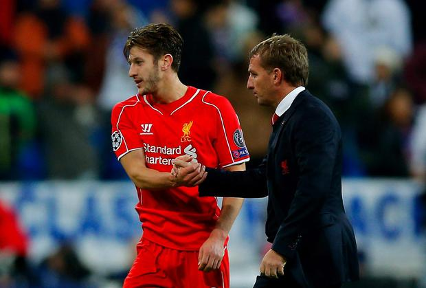 Adam Lallana shakes hands with Liverpool manager Brendan Rodgers after the team's defeat in Madrid