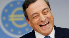President of European Central Bank Mario Draghi, laughs during a news conference in Frankfurt, Germany, Thursday, Nov. 6, 2014, following a meeting of the ECB governing council.