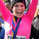 Caroline Wozniacki raises her hands after getting a medal for completing the New York City Marathon