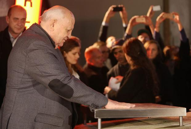 Former Soviet Leader Mikhail Gorbachev, the eighth and last leader of the Soviet Union, places his hands in wet cement attached to a section of the former Berlin Wall as he speaks to Berliners at the former Checkpoint Charlie border crossing amidst days of celebrations for the 25th anniversary of the fall of the Berlin Wall