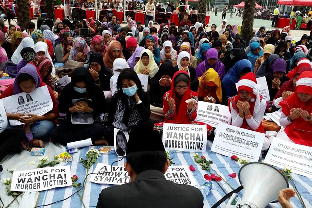 Indonesian women attend a memorial for two murder victims in Hong Kong on Sunday. Rurik Jutting, a British banker charged with killing the two women in Hong Kong. Jutting did not enter a plea on Monday and did not seek bail. A further hearing takes place today (REUTERS/Venus Wu)