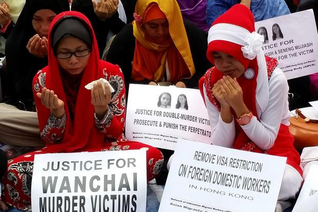 Indonesian women pray during a memorial for two murder victims in Hong Kong on Sunday. Rurik Jutting, a British banker charged with killing the two women in Hong Kong. Jutting did not enter a plea on Monday and did not seek bail. There will be another hearing later today