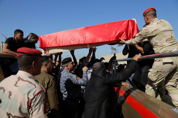 Mourners grieve as the body of police Lt. Gen. Faisal Malik is taken for burial before a funeral procession in Baghdad, Iraq, Saturday, Nov. 8, 2014. A suicide truck bomber targeting a senior police officers convoy in Iraq killed several people late Friday, including the ranking official, authorities said Saturday. (AP Photo/Karim Kadim)