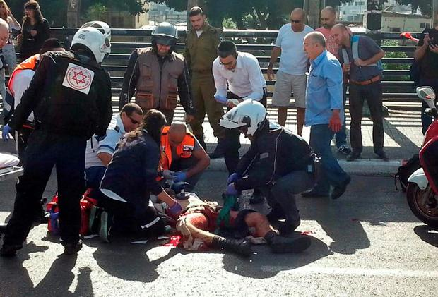 Paramedics treat an Israeli soldier after he was stabbed in Tel Aviv by a Palestinian yesterday. Photo credit: REUTERS/Stringer