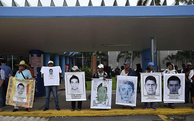 Demonstrators in Acapulco hold pictures of some of the 43 missing students as they block the entrances of the airport during clashes with riot police that erupted during a protest against their suspected massacre