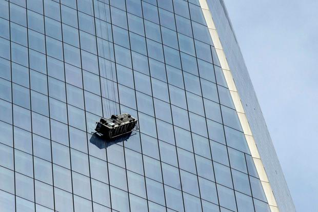 Stranded window washers hang on the side of One World Trade Center November 12, 2014