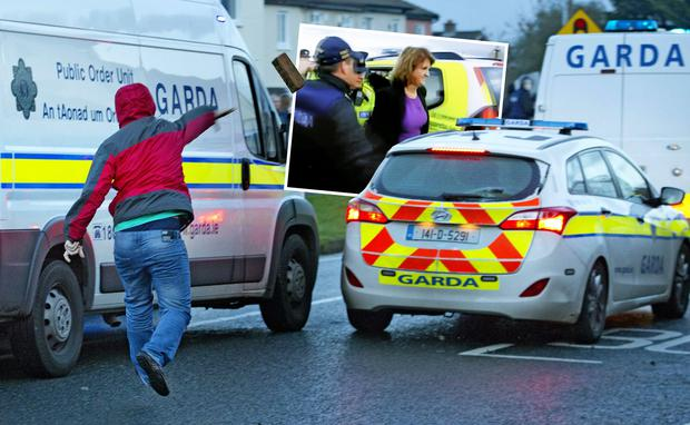 Riot: A man throws a brick at a garda car in Jobstown yesterday. Inset: Gardai lead Ms Burton away, after she was trapped in her car by protesters