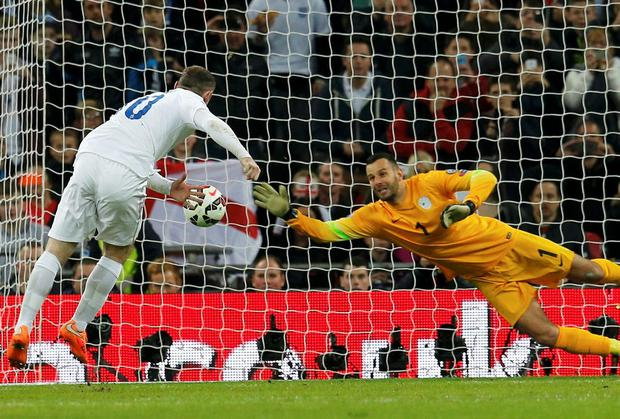 England captain Wayne Rooney shoots to score a penalty past goalkeeper Samir Handanovic