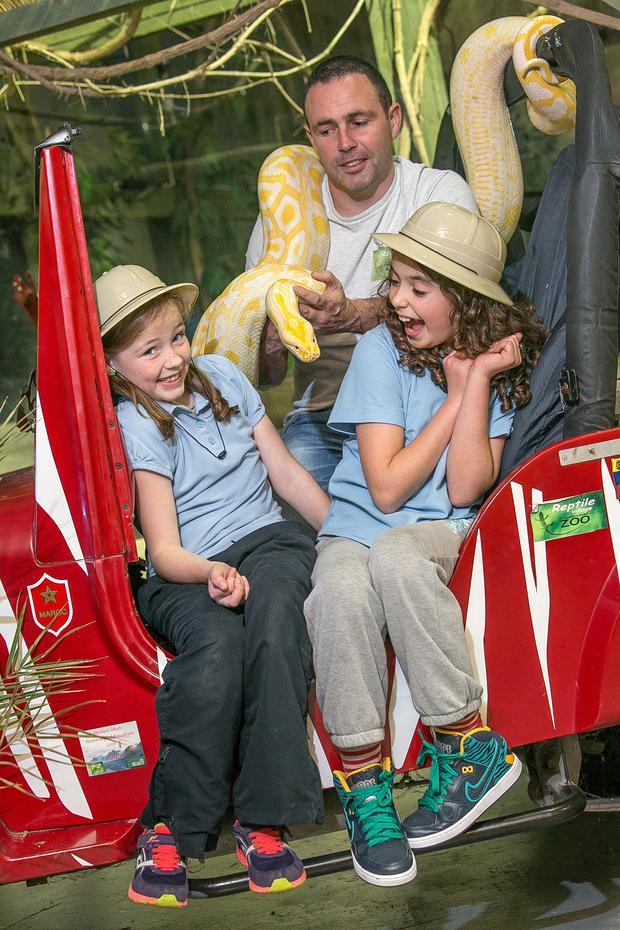 Pictured are James Hennessy, Director and creator of the Reptile Village with nine year olds, Katelyn Hennessy (9) and Heather Dolan as well as Rascal the Burmese python.