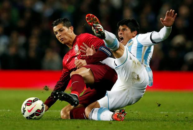 Portugal's Cristiano Ronaldo is challenged by Facundo Roncaglia of Argentina during their friendly at Old Trafford. Photo: REUTERS/Phil Noble