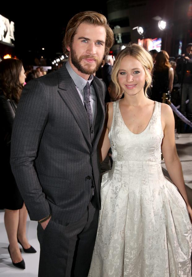 Liam Hemsworth, left, and Jennifer Lawrence arrive at the Los Angeles premiere of